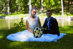 Married couple sitting on grass royalty free stock photo