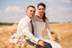 Married couple sitting on haystack. At summer Stock Image