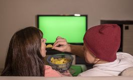 A married couple is sitting at home on the sofa in the evening, watching TV and eating chips stock photography