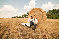 Married couple sitting near haystack on field Royalty Free Stock Images