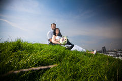 Married couple sitting on top of hill and looking at sky Stock Image