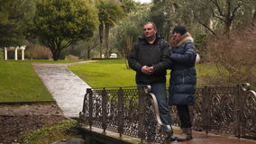 A married couple is standing on a decorative bridge. stock video