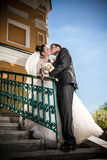 Married couple standing on stairs and kissing Stock Photos