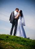 married couple standing on top of hill against blue sky Royalty Free Stock Photography