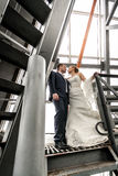 Married couple standing on top of metal stairs Stock Images