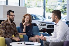 Married couple talking to a car dealer in a showroom. Concept royalty free stock photos