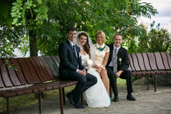 Married couple and two witnesses sitting on bench at park Stock Photography