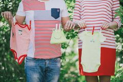 Married couple waiting for a baby-girl. Baby clothes hanging on a rope Royalty Free Stock Photo