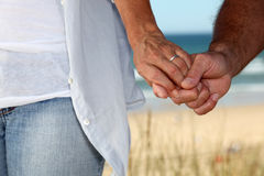 Married couple walking along beach Stock Photos