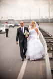 Married couple walking on empty highway Stock Images