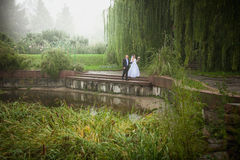 Married couple walking on riverbank at foggy day Royalty Free Stock Images