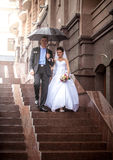 Married couple walking under umbrella on stairway Royalty Free Stock Images
