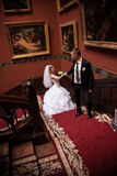Married couple walking up the stairs with red carpet at palace Royalty Free Stock Photo