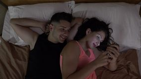 Married couple watching a funny video on social media on a smartphone on the bed at home stock video footage