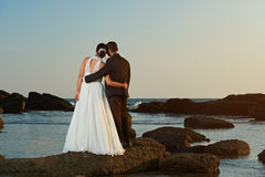 Married couple watching sunset on ocean beach. View from back. Groom and bride hugging on ocean coastline Stock Images