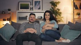 Married couple watching TV sitting on couch in house smiling looking at camera stock footage