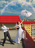 Married couple with white umbrella on the roof. The newly married couple with white umbrella standing on the roof of house under cloudy sky with rainbow  in the Royalty Free Stock Image