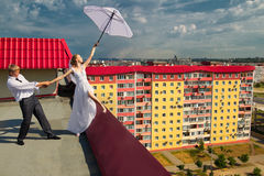 Married couple with white umbrella on the roof. The newly married couple with white umbrella standing on the roof of house under cloudy sky Royalty Free Stock Image