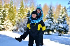 A married loving couple fooling around in a snowy forest on a Sunny winter royalty free stock images