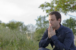 Married man praying outside in a grassy field. Stock Photos