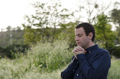 Married man praying outside in a grassy field. Stock Photo