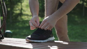 A married man tying shoelaces. The shoes are sneakers. It is a sunny summer days. He is in a park. There is no face stock video footage