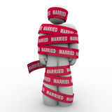 Married Man Wrapped Red Tape Prisoner Trapped Person. An unhappy man is wrapped in red tape with the word Married to illustrate being trapped or caught in an Royalty Free Stock Photos