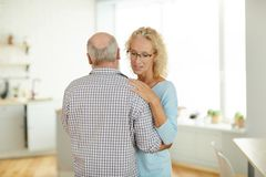 Married mature couple dancing in kitchen stock image