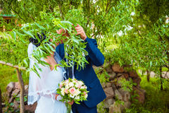 Married Newlyweds hiding behind branch with leaves Royalty Free Stock Photo