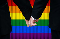 Married with Pride. Two gay men stand hand in hand before a marriage altar featuring an overlay of pride flag colors, having just been legally married under royalty free stock photos