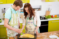 Married smiling couple cooking apple pie at the kitchen Royalty Free Stock Photos