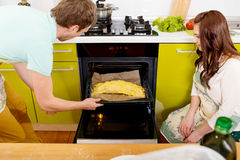 Married smiling couple putting apple to the oven at the kitchen Royalty Free Stock Photos