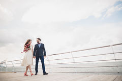 Married wedding couple standing on a wharf over the sea.  Stock Photo