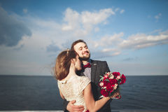 Married wedding couple standing on a wharf over the sea Stock Images