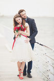 Married wedding couple standing on a wharf over the sea.  Stock Photography