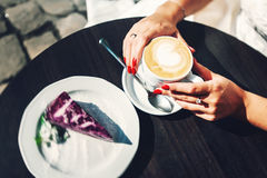Married woman drinking coffee at the cafe patio at the sunrise. Red manicure. Selective focus Royalty Free Stock Image