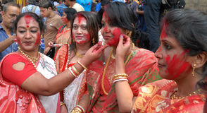 Married Women. Married Bengali Hindu women smear and play with vermilion during Sindur Khela traditional ceremony on the final day of Durga Puja festival on Stock Image