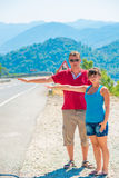 Married young couple hitchhiking. Summer day Royalty Free Stock Photography