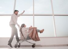 Married young couple riding in shopping cart. Photo with copy space stock photo