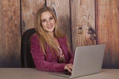 Marrone rossiccio dell'ufficio del computer della donna felice fotografia stock