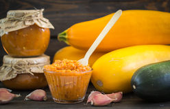 Marrow paste in banks and in a bowl, garlic, and zucchini Royalty Free Stock Photo