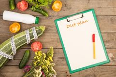 Marrow squash, measure tape, clipboard with inscription & x22;Diet plan& x22;, bottle of water, flowers, tomatoes and cucumbers stock image