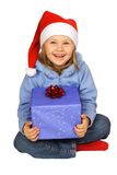 Marry Christmas!. Girl in red Santa Claus hat keep a blue box with red bow Stock Image