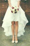 Marry, marriage. Bride outdoors. Bridal bouquet in street. Figure of a woman with a bouquet of flowers in her hand in front of a bricks wall in the city stock photo