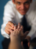 Marry me?. A man proposing and putting a ring on a woman's finger Stock Photo