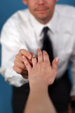 Marry Me?. A man proposing and putting a ring on a woman's finger Royalty Free Stock Image