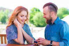 Marry me concept. Loving couple getting engaged in an outdoor cafe. Man making proposal to his girlfriend stock photos