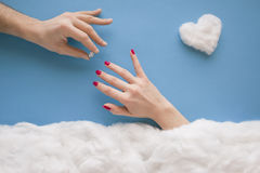 Marry me. Man hand putting ring on women`s finger, in a heavenly scenery with a heart and clouds made from cotton wool, on a blue sky paper background stock images