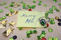 Marry Me ring. Year beautiful sparkles stars, jewel emerald ring with emerald ring green design, gift vintage christmas white celebration, decoration, holiday Stock Image