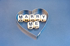 Marry me. Text message, ' Marry me ' with black upper case letters on small white cubes inside a silver heart shape  on a gray background Royalty Free Stock Images